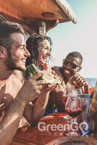 Man eating watermelon on Galapagos Cruise and group drinking sangria