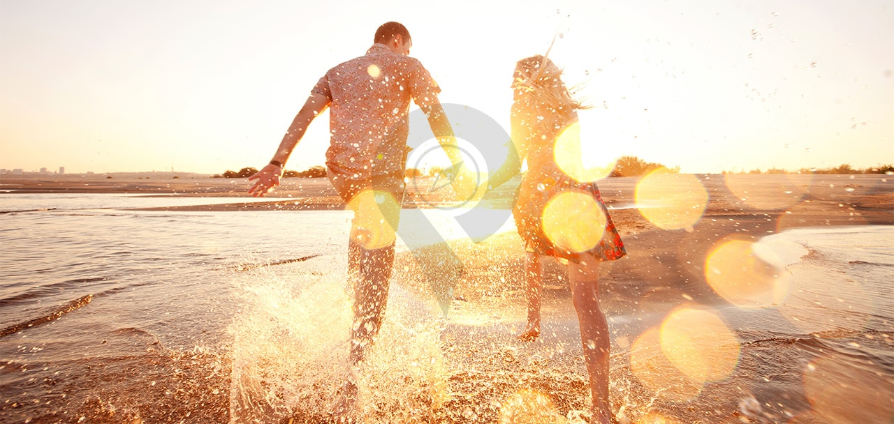 Galapagos-honeymoon-Couple-running-through-the-ocean-holding-hands-during-sunset