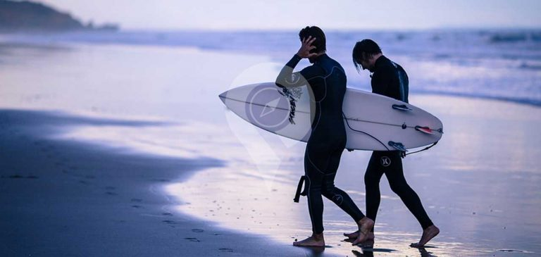 Galapagos wetsuits - surfers walking on beach